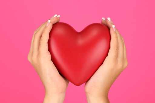 Red heart in woman's hands, on pink background close-up